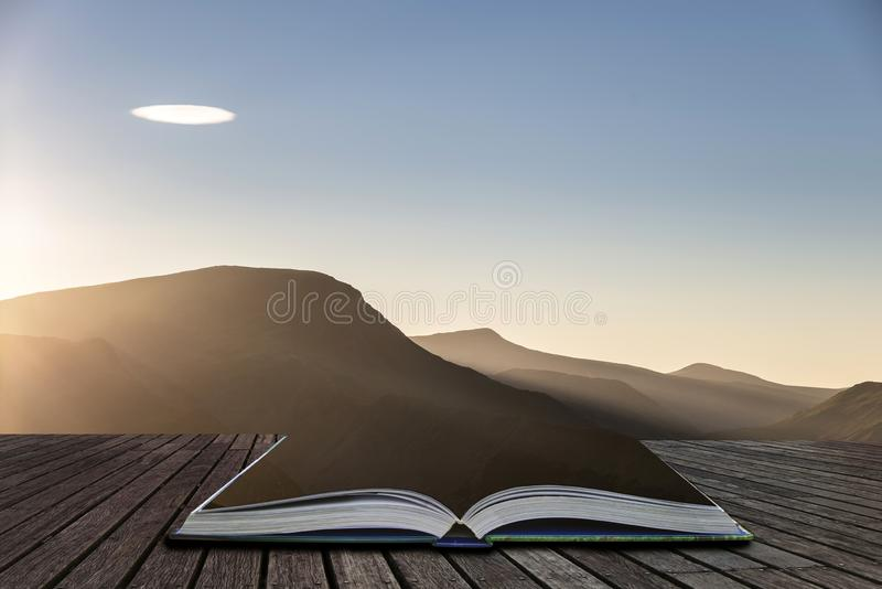 Beautiful Autumn Fall landscape image of sun beams lighting up small area of mountain side in Lake District coming out of pages of royalty free stock images