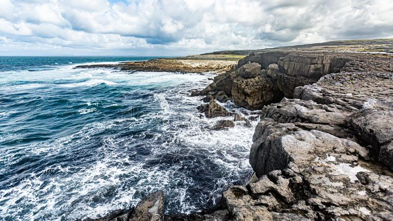Stunning landscape of sea cliffs in Bothar nA hAillite. Geopark and geosites, Wild Atlantic Way, beautiful cloudy spring day in County Clare in Ireland royalty free stock photo