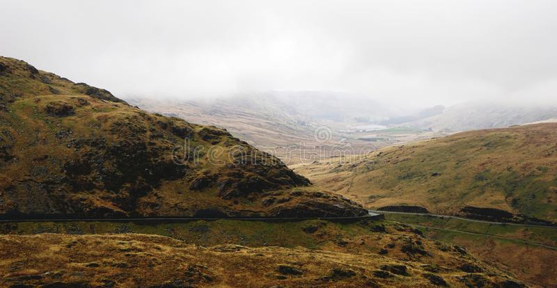 Stunning Landscape in Snowdon, Wales, United Kingdom. Stunning landscape with foggy and moody skies among beautiful mountains – captured during a hike at stock photography