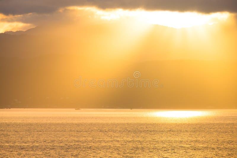 Stunning landscape sunrise in the morning. Golden light go through the cloud to the mountain and sea. I. Stunning landscape sunrise  in the morning. Golden light stock photo