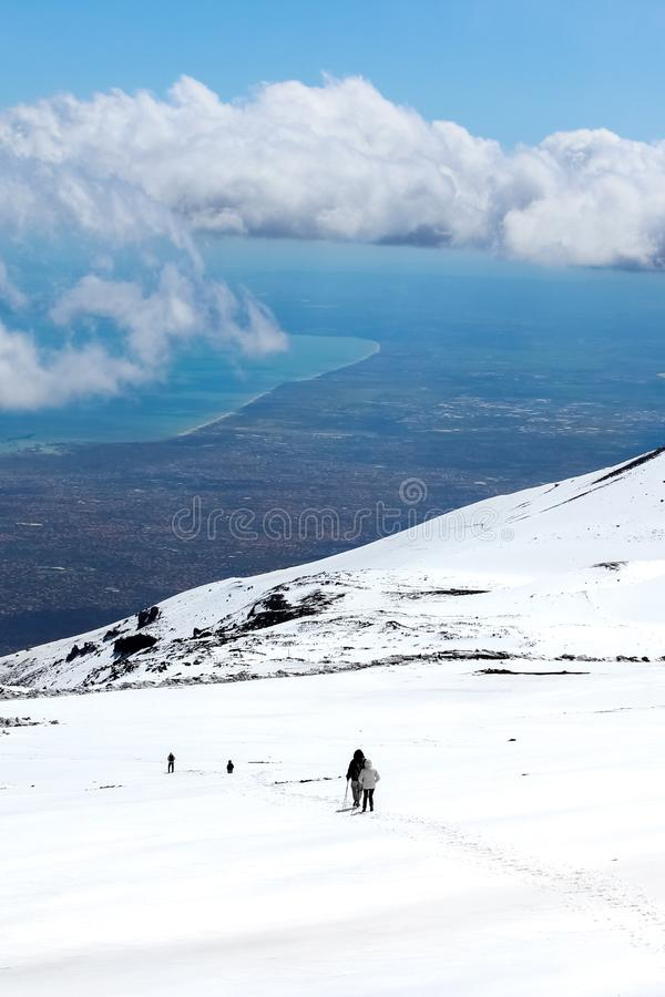 Stunning landscape taken from Mount Etna, Sicily, Italy. Hikers on the way down from the volcano. Snow on the mountain. Sicilian. Sea coast in the background royalty free stock photos