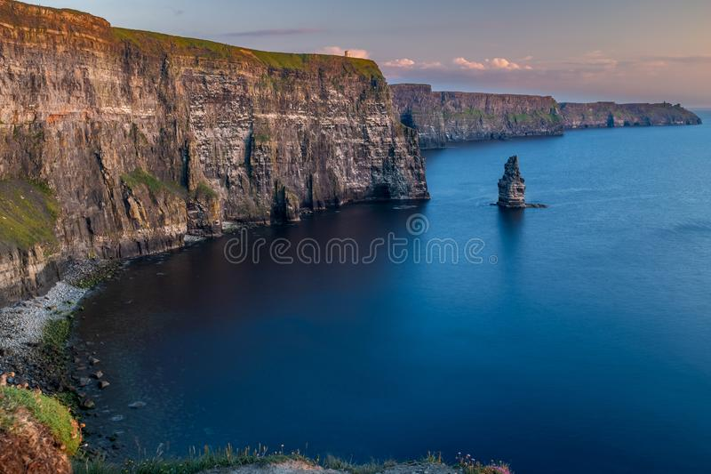 The stunning and majestic Cliffs of Moher in County Clare, Ireland at sunset, beautiful pink sky taken from Luca Lookout royalty free stock images