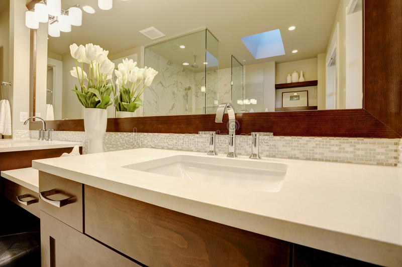 Stunning master bathroom boasts dark brown double sink vanity. Topped with white marble framing his and her sinks paired with mosaic backsplash under dark brown stock photo