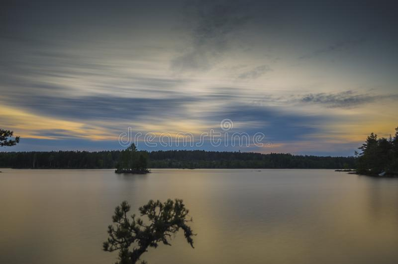 Stunning movement of blue cloud on a countryside lake during the sunset through the orange horizon in beautiful summer day royalty free stock photography