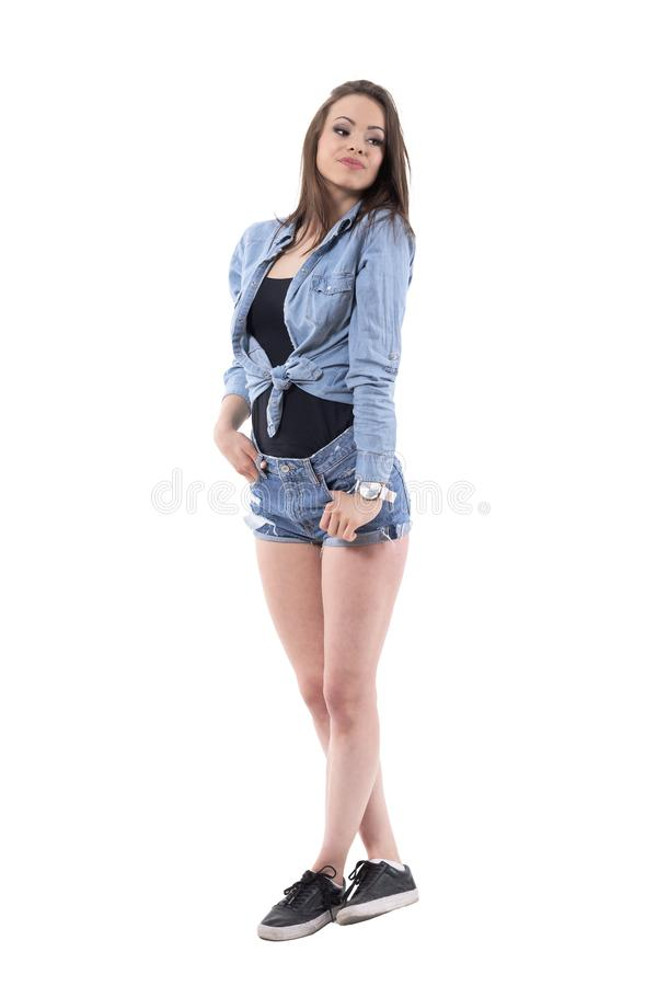 Stunning multi ethnic latin beauty posing in denim torn shorts looking back over shoulder. royalty free stock images