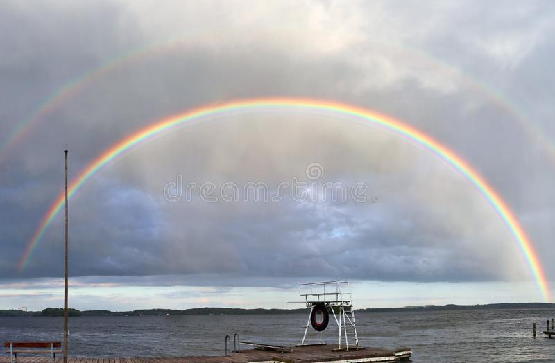 Stunning natural double rainbows plus supernumerary bows seen at a lake in northern germany royalty free stock photography
