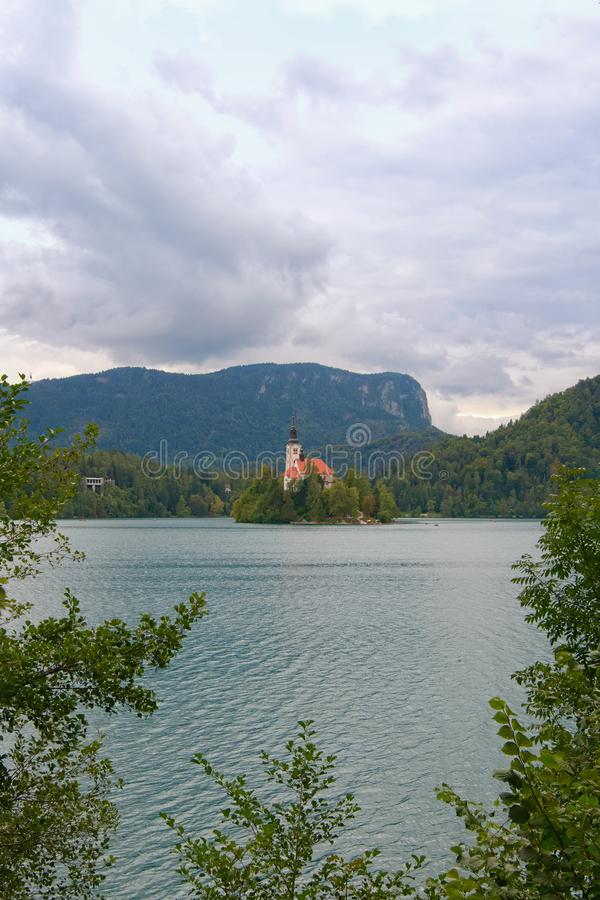Stunning nature landscape of Bled Lake with St. Marys Church of Assumption on small island. Natural frame form green leaves royalty free stock image