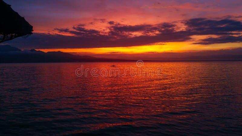Stunning sunset over Samboan in Cebu Island in Philippines. Stunning orange sunset over cloudy sky at Samboan in Cebu Island in Philippines stock image