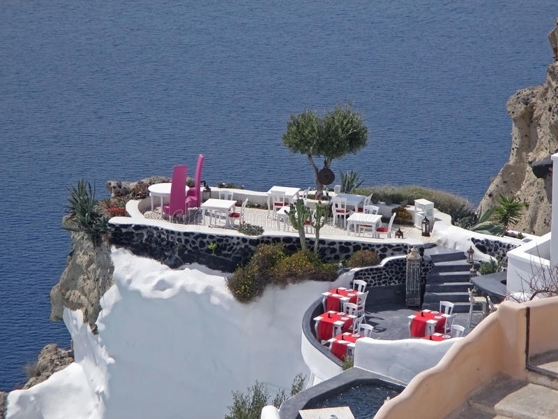 Stunning outdoor seating at the terrace over the caldera on vibrant blue Aegean sea, Santorini island royalty free stock image