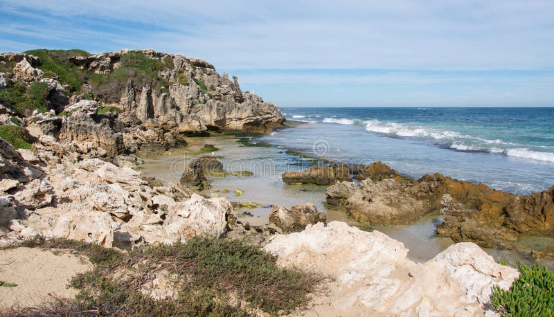 Stunning Penguin Island. Rugged vegetated limestone outcroppings with the Indian Ocean waves rolling in at Penguin Island under a blue sky with clouds in royalty free stock image