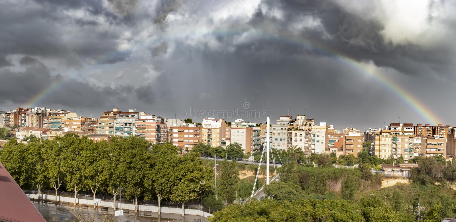 Stunning rainbow appearing through the clouds after a thunderstorm in a city. Image taken in Esplugues de Llobregat, Spain royalty free stock photos