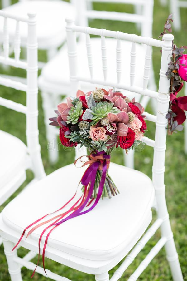 Stunning red bridal bouquet on white chair. Wedding ceremony. Mix of succulents, orchids and roses royalty free stock photography