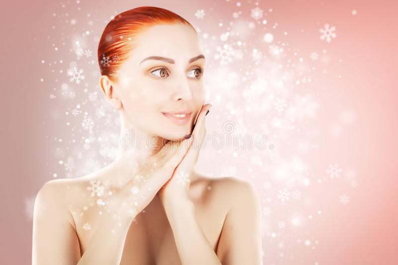 Stunning red haired woman over christmas pink background stock images