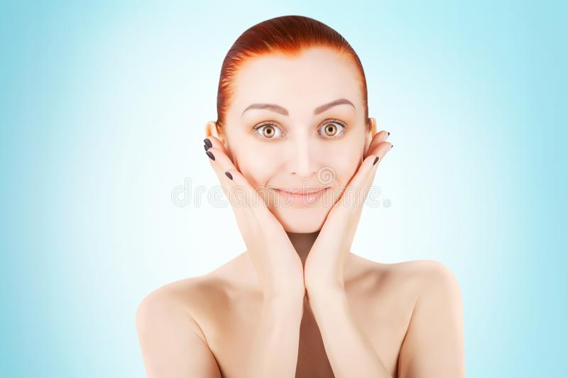 Stunning red haired woman skin health concept, blue background stock photography