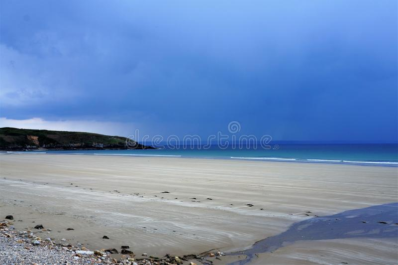 Stunning reflection of sunlight at the beach when rainclouds are forming above the sea stock image