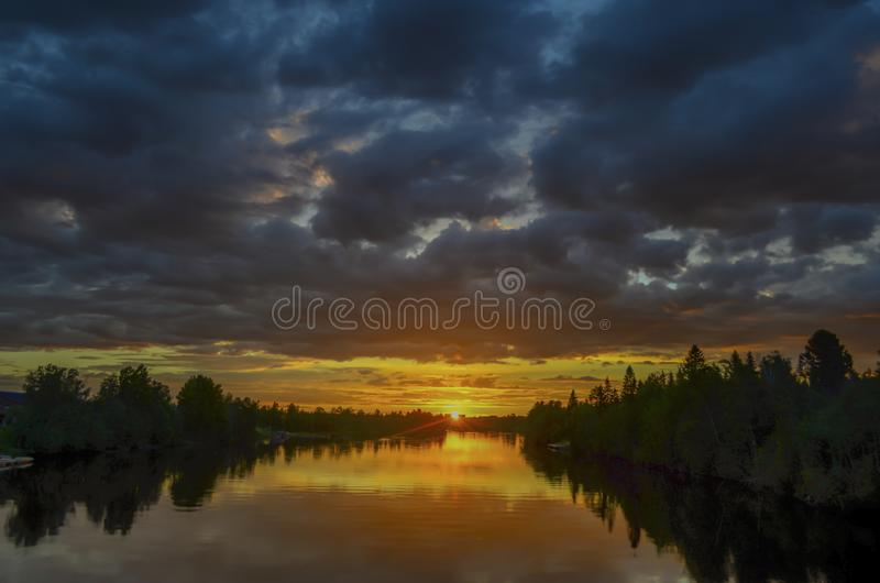 Stunning reflection of sunlight on moving cloud and reflection on the river through the orange horizon in beatiful summer day royalty free stock photography