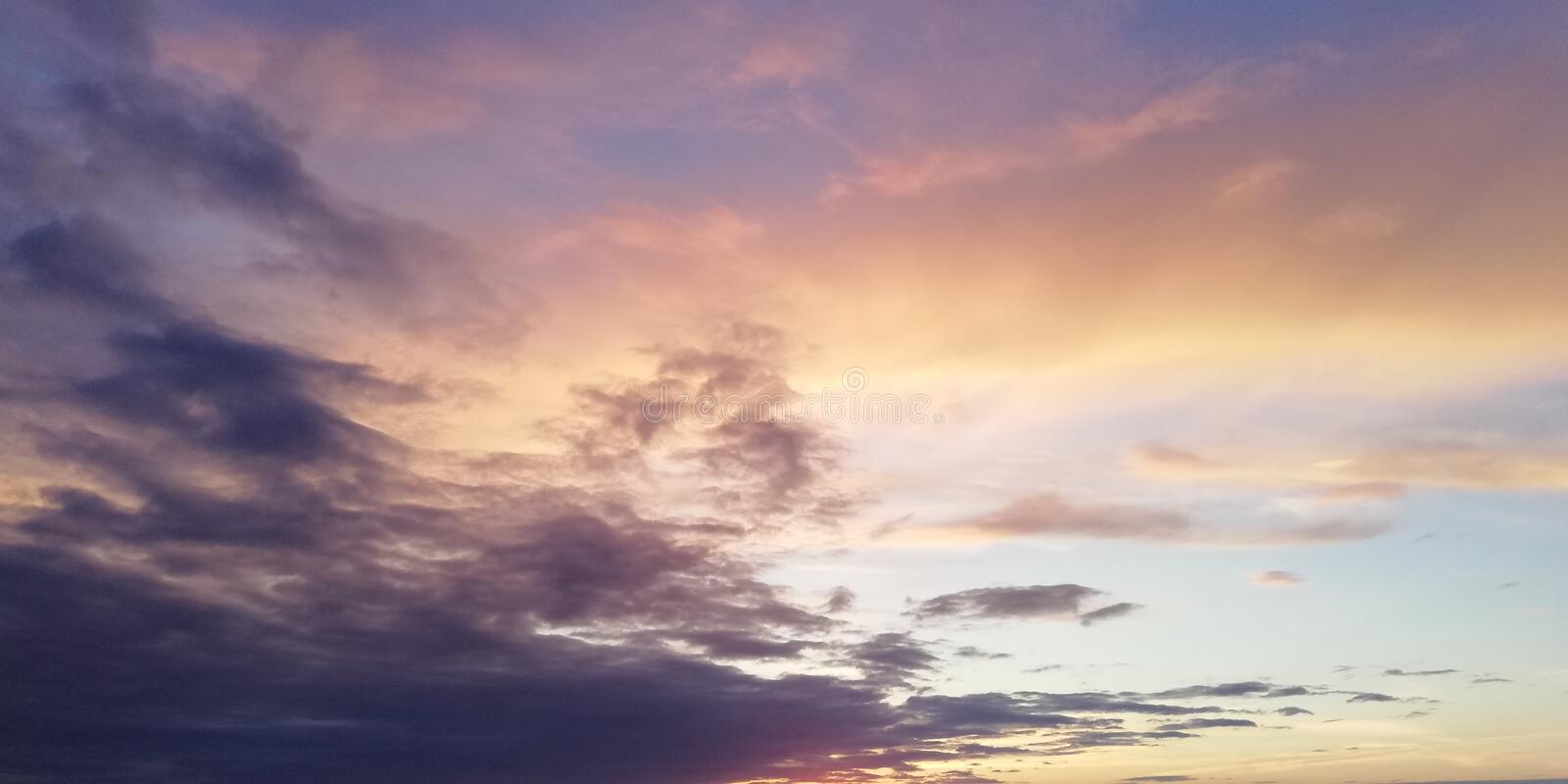 Stunning scenic backdrop. Multicolored clouds in the sunset sky. Light clouds contrast with dark clouds stock photos