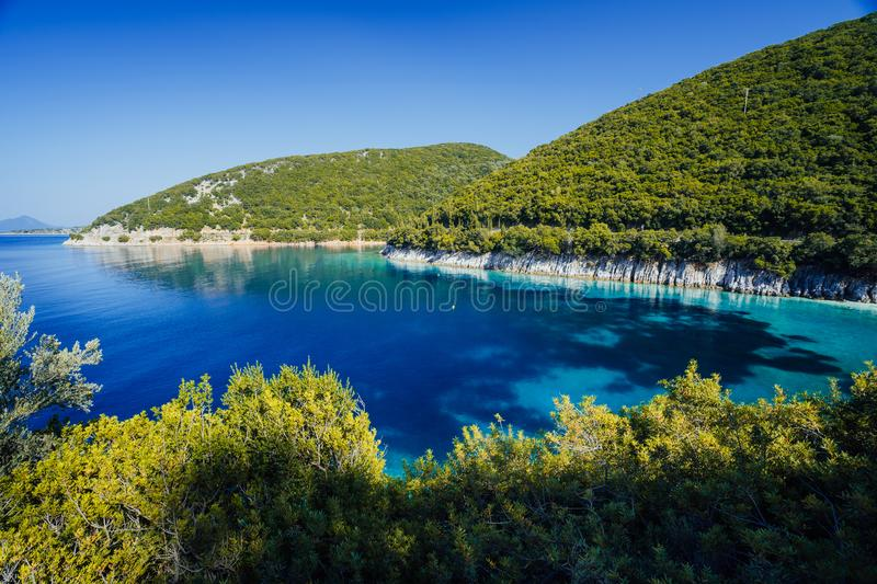 Stunning seaside scenery of the cove with turquoise calm sea water, surrounded by hills overgrown with pine and olive royalty free stock photography