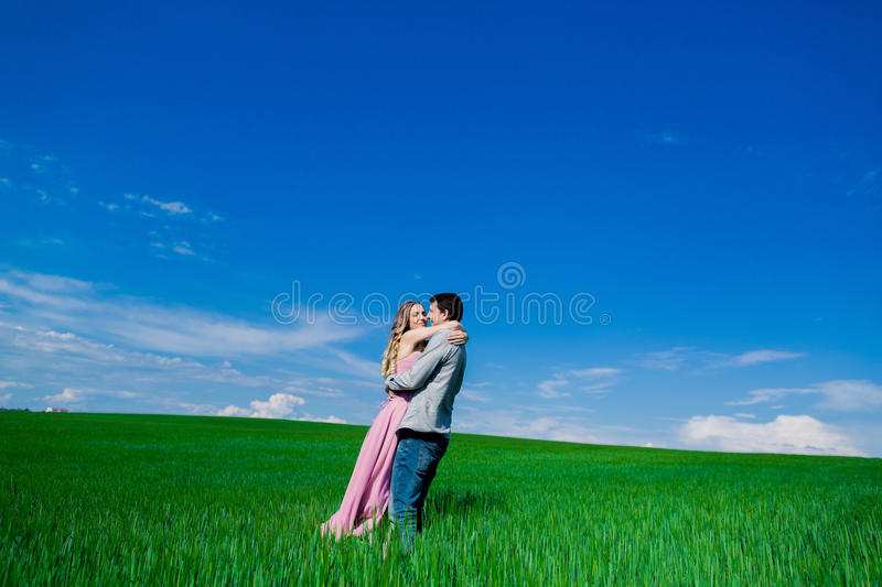 Stunning sensual outdoor portrait of young stylish fashion attractive couple in love kissing in summer field.  royalty free stock images