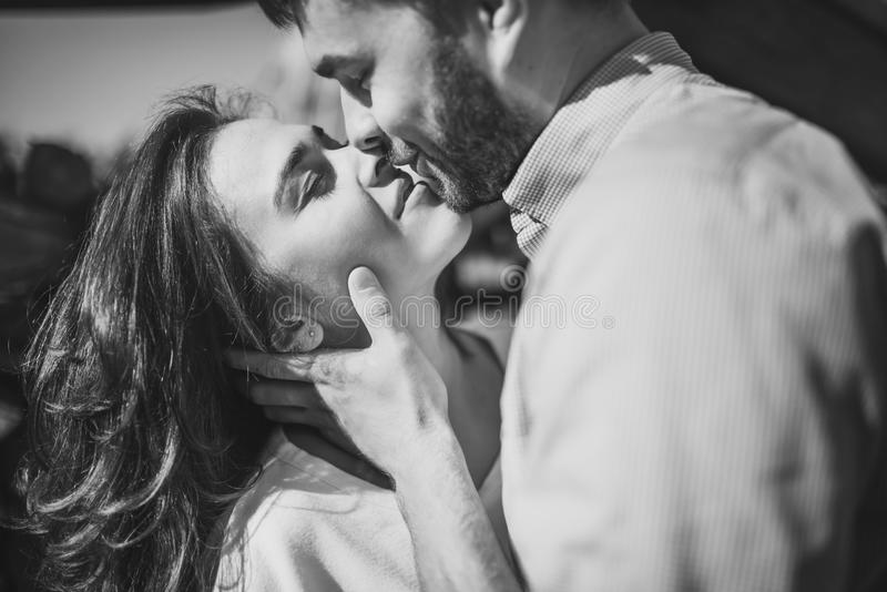 Stunning sensual outdoorblack and white portrait of young stylish fashion couple in love. Woman and man embrace and want to kiss. royalty free stock image