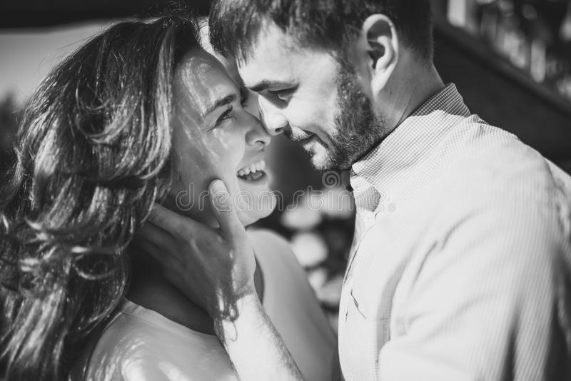 Stunning sensual outdoorblack and white portrait of young stylish fashion couple in love. Woman and man embrace and want to kiss. stock photo