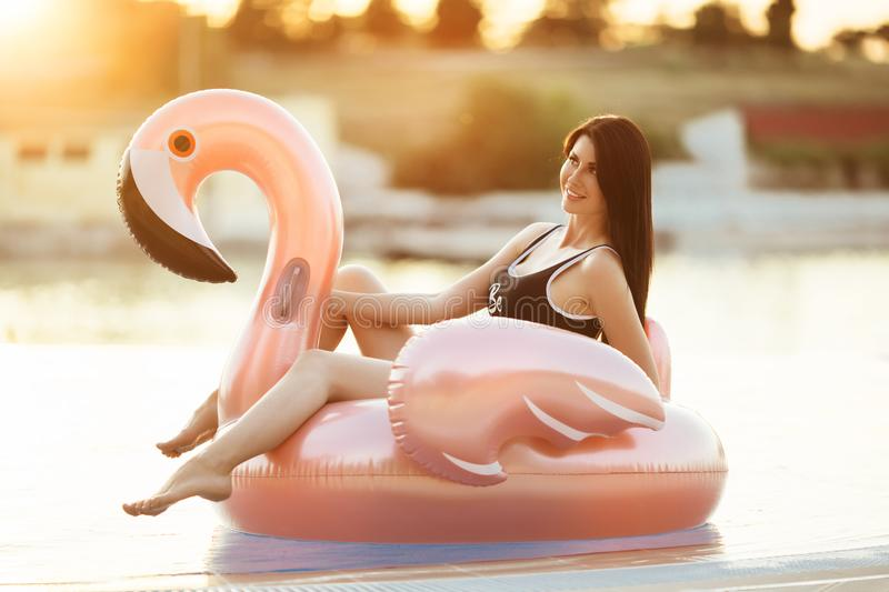 Stunning slim girl is wearing black bikini sitting in swimming pool with blue water on a pink flamingo mattress over royalty free stock photos