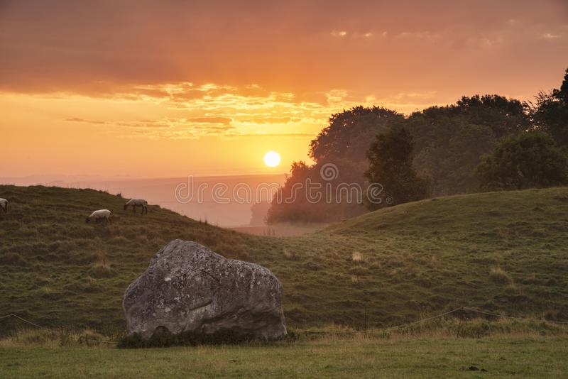 Stunning Summer sunrise landscape of Neolithic standing stones in English cluntryside with gorgeous light with slight background stock image