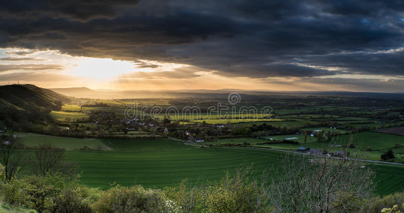 Stunning Summer sunset across countryside landscape with dramatic clouds stock images