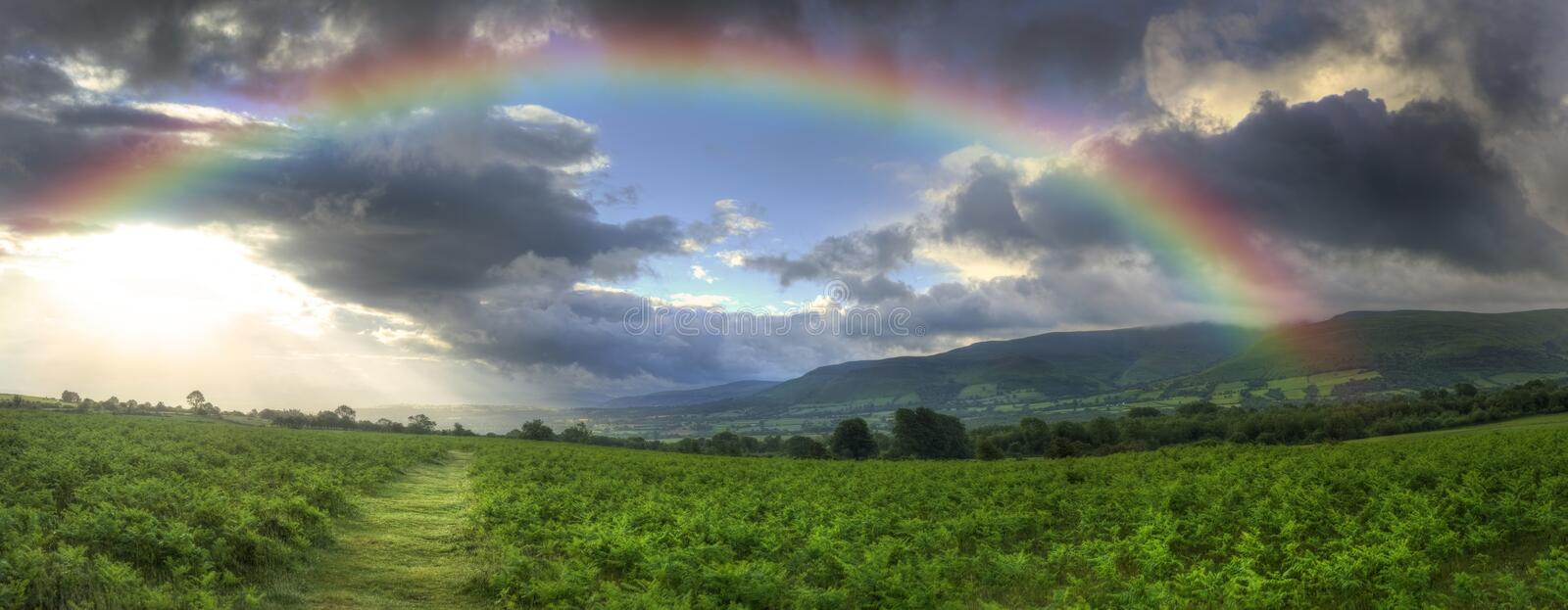 Stunning Summer sunset across countryside landscape with dramatic rainbow royalty free stock image