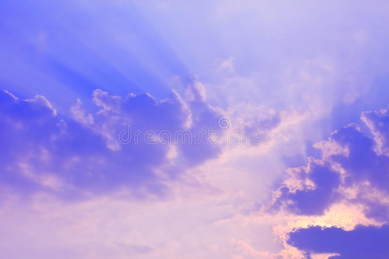 Stunning sun light shines through the cloud in a bright blue sky royalty free stock photography