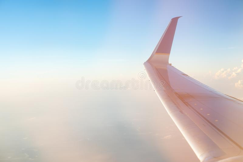 Stunning sunrise view on a high altitude from the passenger window of a conventional airplane. The morning sun colors. The sky in pastel royalty free stock photos