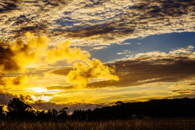 Stunning sunset in the field. Cloudy and orange sky stock images