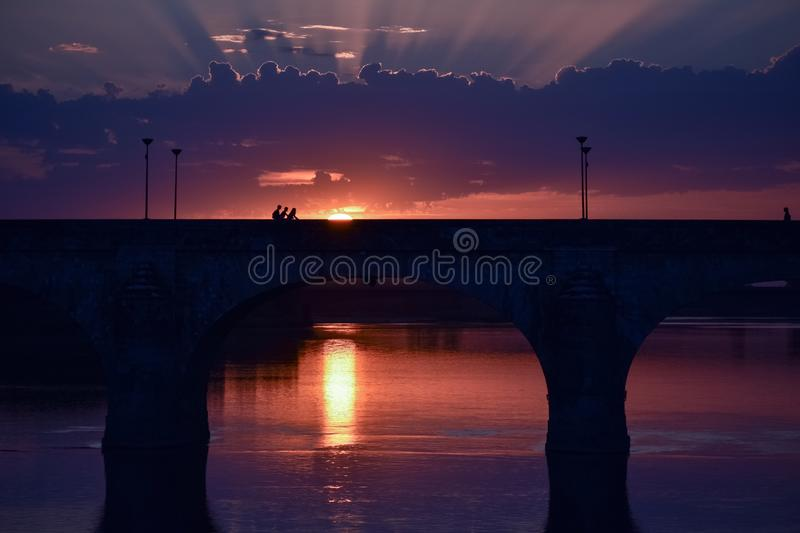 Stunning sunset with light coming through the clouds and a colorful sky. In the foreground a bridge of a city in backlighting. France royalty free stock images