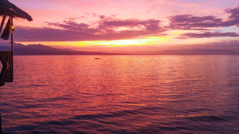 Stunning sunset over Samboan in Cebu Island in Philippines. Stunning orange sunset over cloudy sky at Samboan in Cebu Island in Philippines royalty free stock photo