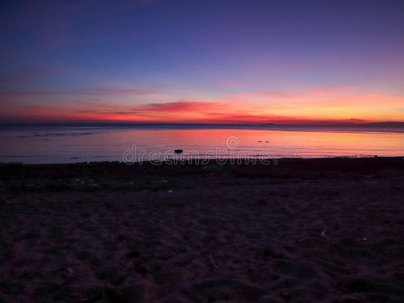 Stunning sunset over Samboan in Cebu Island in Philippines. Stunning orange sunset over cloudy sky at Samboan in Cebu Island in Philippines royalty free stock image
