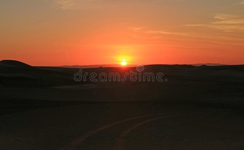 Stunning sunset over the sand dune of Huacachina desert with people and dune buggy in distance, Ica region, Peru stock photos