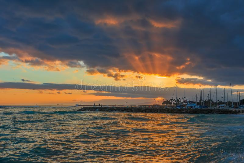 Stunning sunset with rays of sunlight shining through storm clouds in Oahu, Hawaii stock photography