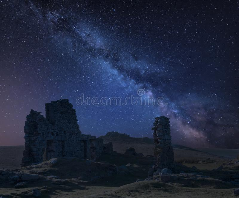 Stunning vibrant Milky Way composite image over abandoned Foggintor Quarry in Dartmoor with raking soft sunlight over ruins and. Derelict buildings stock photography