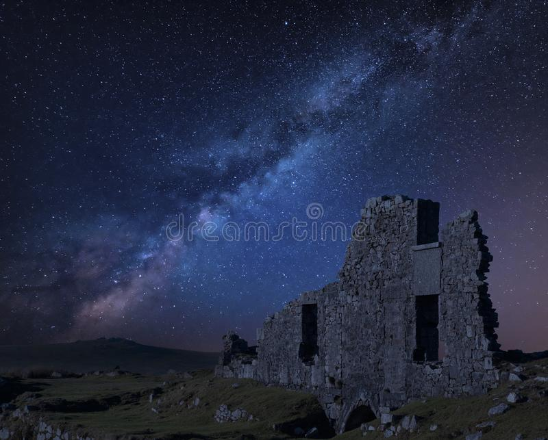 Stunning vibrant Milky Way composite image over abandoned Foggintor Quarry in Dartmoor with raking soft sunlight over ruins and. Derelict buildings royalty free stock photos