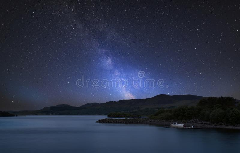 Stunning vibrant Milky Way composite image over landscape of calm lake with boat on shore royalty free stock photography