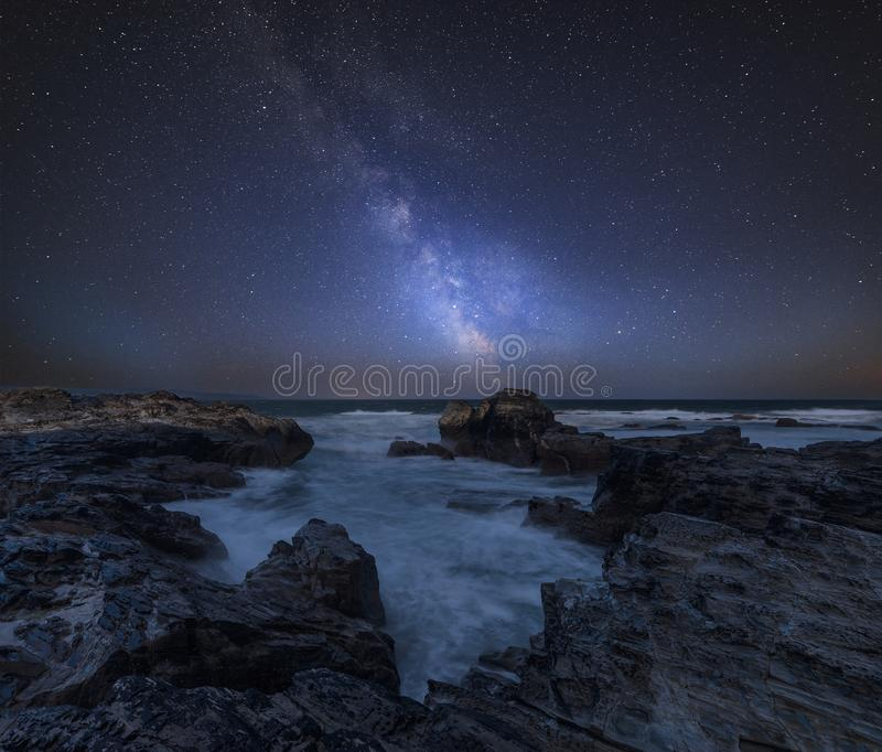 Vibrant Milky Way composite image over landscape of Cornwall coastline in England stock photography