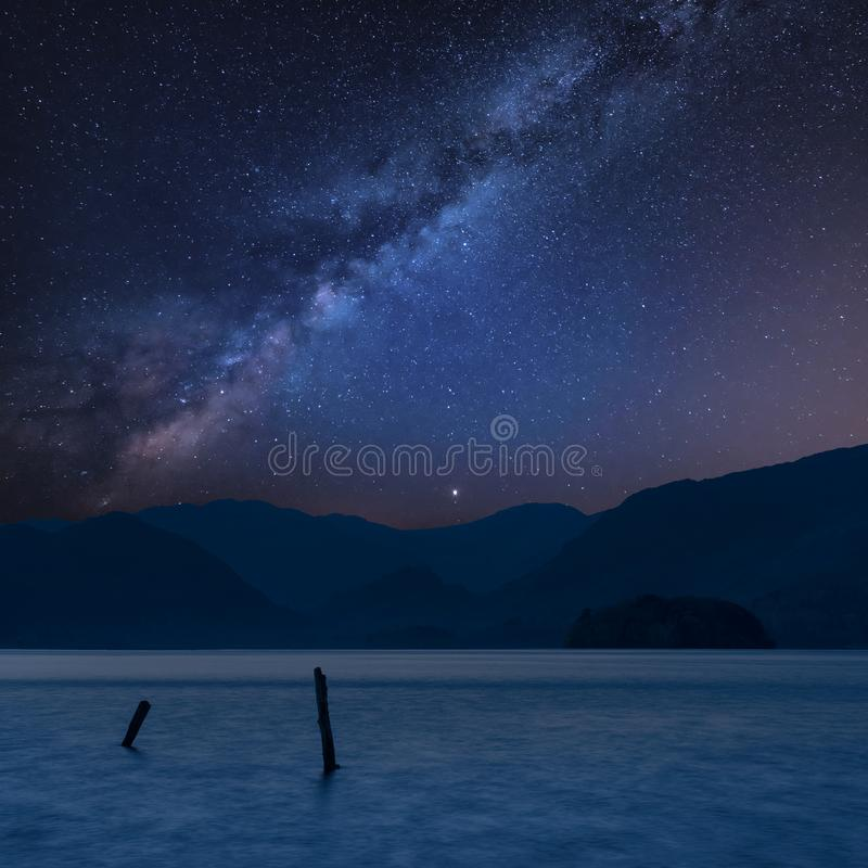 Stunning vibrant Milky Way composite landscape image over Derwent Water in Lake District during Autumn Fall sunrise with soft stock photography