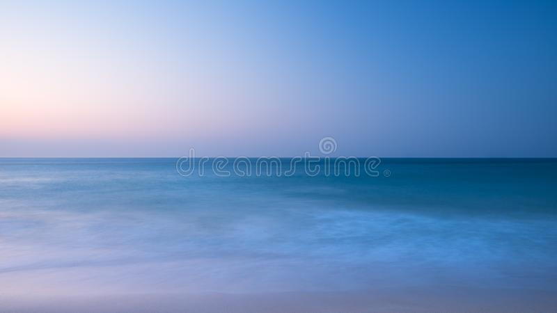 Stunning vibrantl sunrise landscape image of calm sea looking out from Porthcurno beach on South Cornwall coast in England stock photo