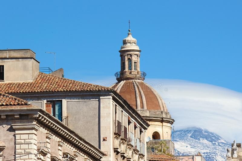 Stunning view of Catania Cathedral of Saint Agatha in Catania, Sicily, Italy. Mount Etna volcano with snow on the very top. In the background. Beautiful piece royalty free stock photography