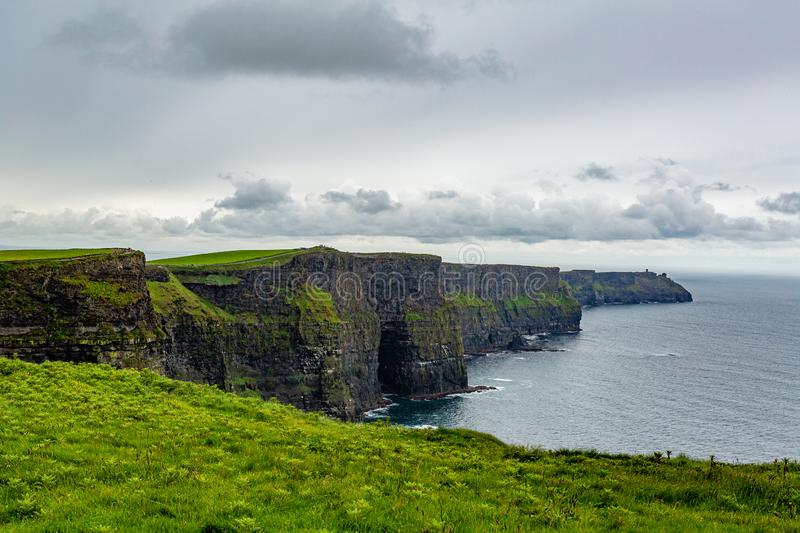 Stunning view of the Cliffs of Moher from a hill. Geosites and geopark, Wild Atlantic Way, wonderful spring cloudy day in the countryside in county Clare in stock image