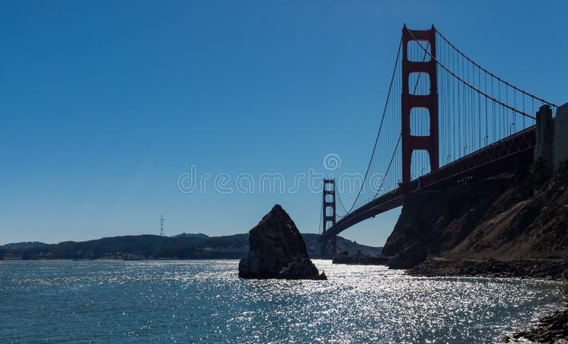 Stunning view of famous Golden Gate Bridge seen from scenic Baker Beach against a bright blue sky on a sunny day, San. A low angle view of the stunning famous royalty free stock photo