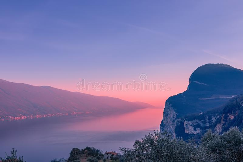 Stunning view of Lake Garda in the evening fog and the light of the setting sun. Winter period. View from the mountain town. Tremosine, Garda Lake, Lombardy stock image
