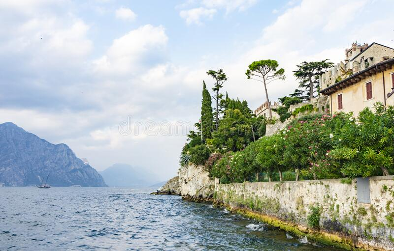 A stunning view of Lake Garda near the city of Malcesine. Cozy European Italian old town above a mountain lake with abundant royalty free stock photography