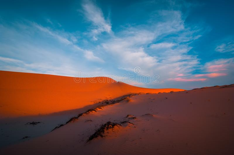 Stunning view of lonely sand dunes under amazing evening sunset sky royalty free stock photo