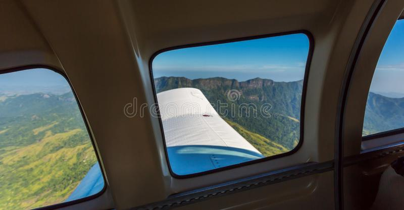 Stunning view of mountain range from a window of a small airplane during take off. Air travel in Fiji, Melanesia, Oceania. Green lush vegetation on emerald royalty free stock photo